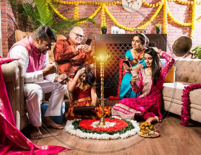 Multigenerational Indian Family Addicted To Mobile Phone Or Using Smartphone In Diwali Festival