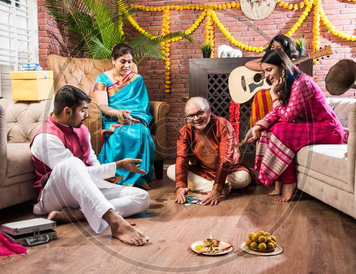 Indian Family Playing Three Cards Or Teen Patti In Diwali Or Deepavali Festival At Home
