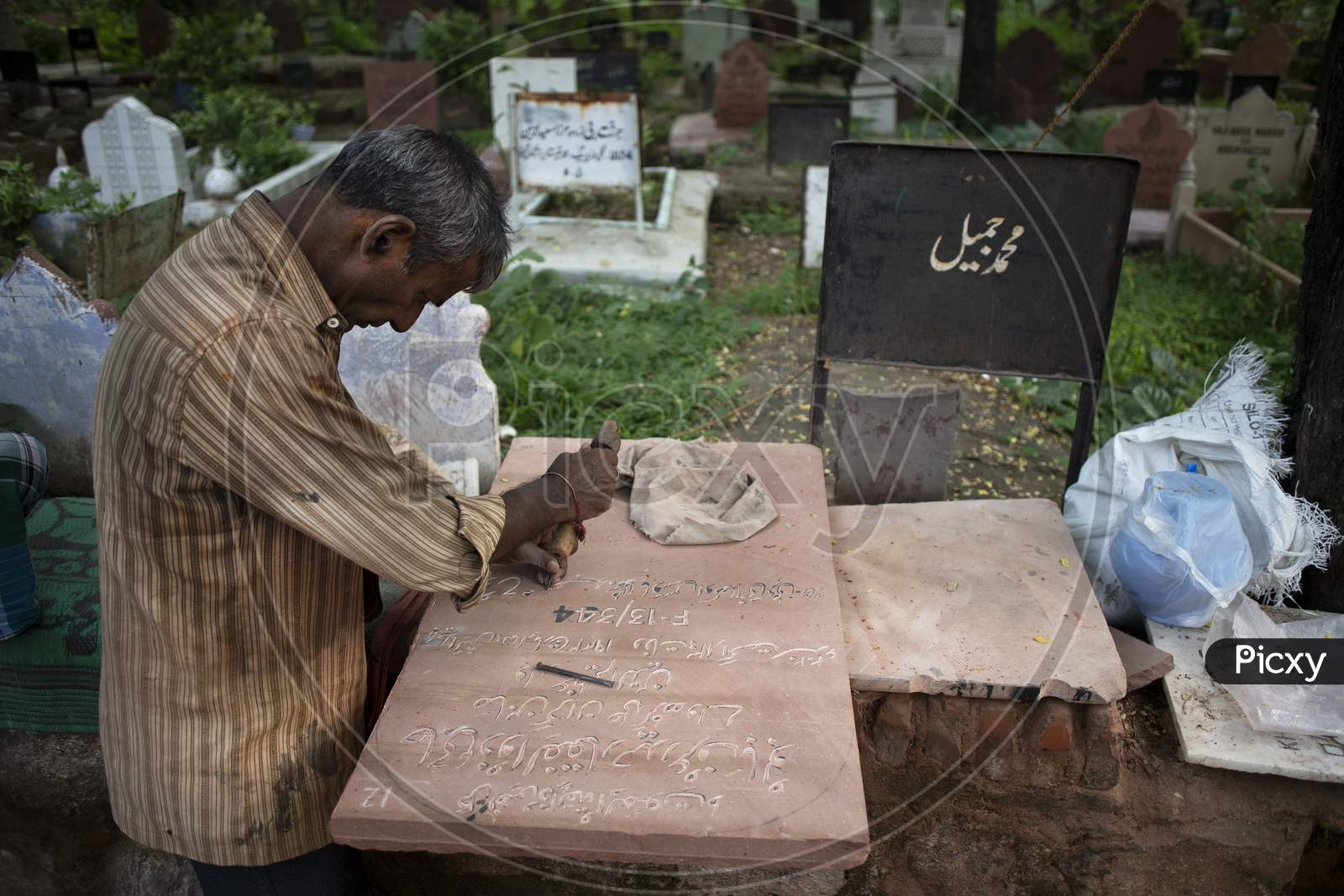 A tombstone maker engraves a tombstone of a Covid -19 victim near a graveyard in New Delhi, India, on September 14, 2020.