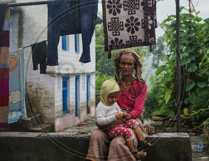 Almora, India - September 06, 2020: Portrait Of An Old Woman, Wearing Old Rugged Saree Holding A Kid In Her Lap.