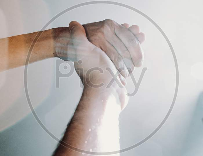 Young Hand Grabbing An Old Woman Hand With A Light Flare Breaking In