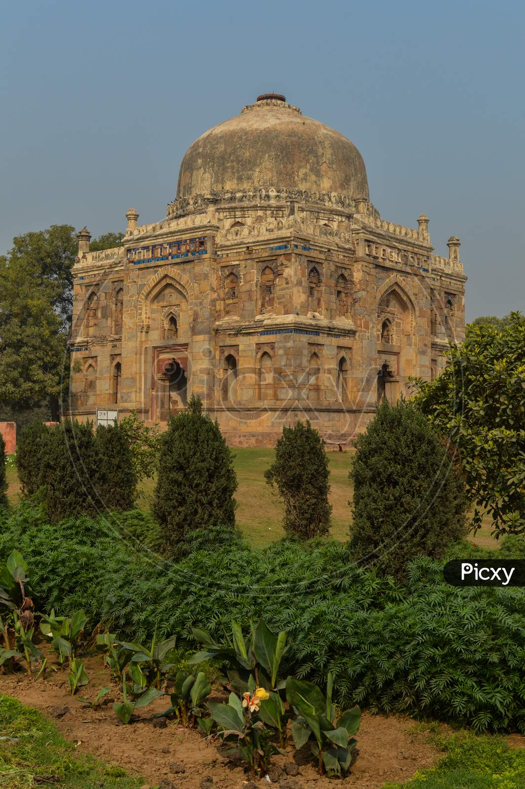 A Shish Gumbad Monument At Lodi Garden Or Lodhi Gardens In A City Park From The Side Of The Lawn At Winter Foggy Morning.