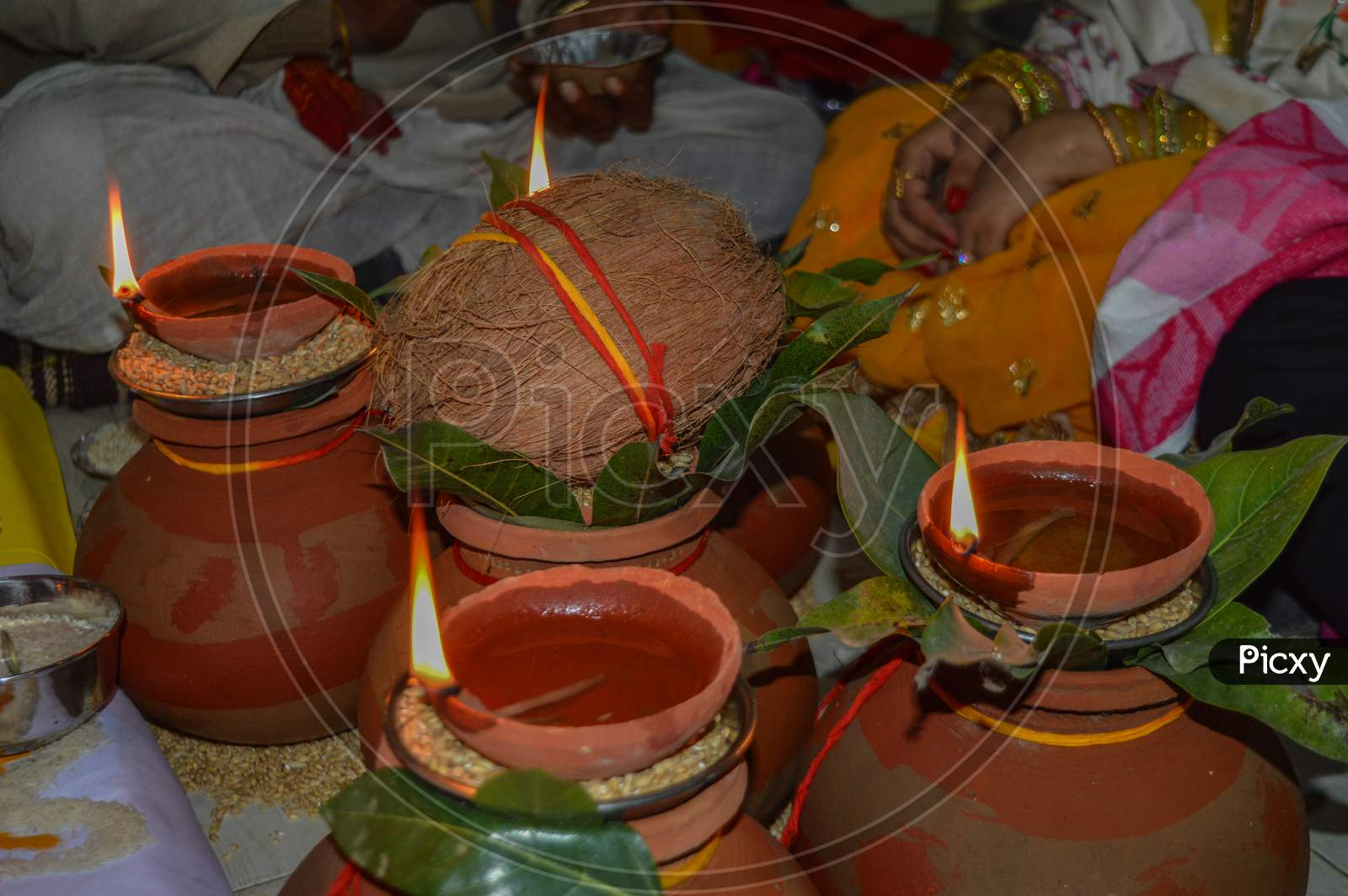 Clay Pot With Coconut, Mango Tree Leaf, Oil, Rice, Wheat Lit Up For Worship Of Indian God.