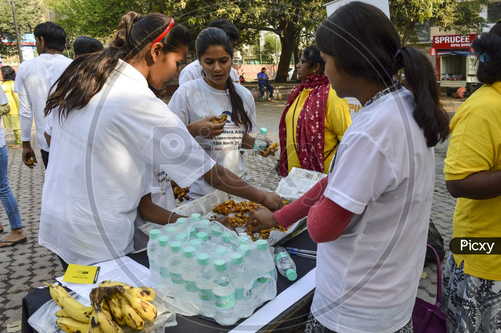 A Group Of Indian People Having The Food At Event For Support The Cycle Ride To Celebrate International Women'S Day.