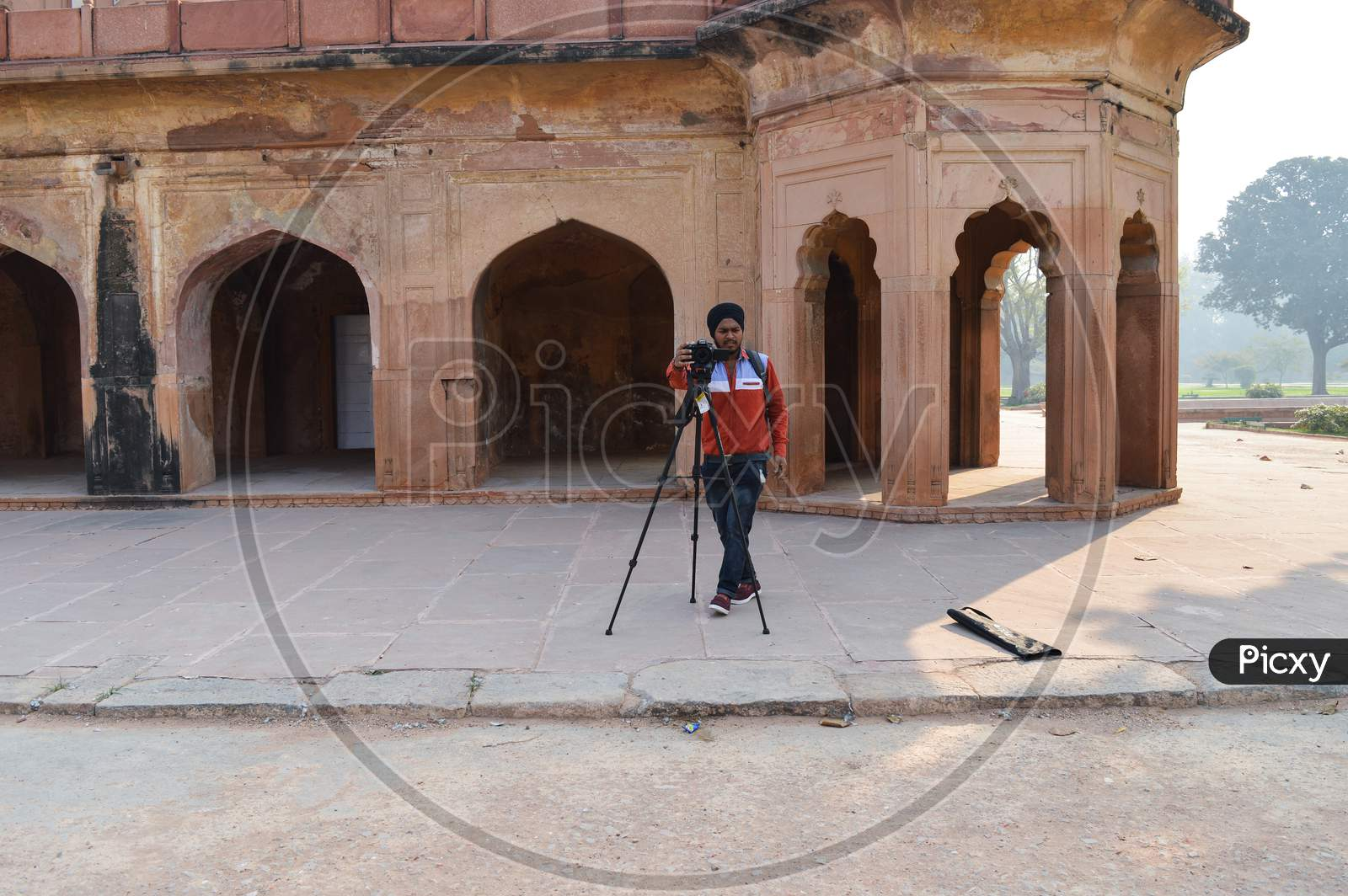 A Photography Student Trying To Take Group Picture Of Students With Tripod Out Side Of Safadarjung Tomb Memorial At Foggy Winter Morning.