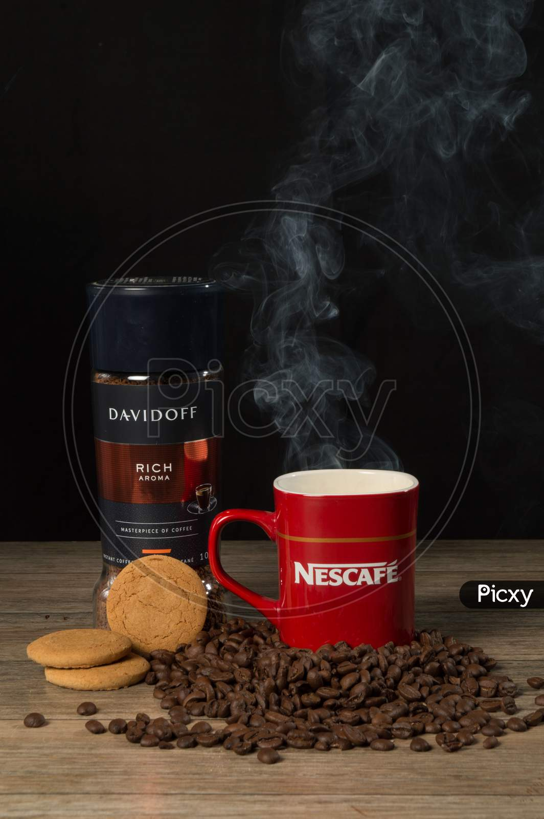 Smoky Coffee In Red Nescafe Mug With Raw Coffee Beans, Cookies, David Off Coffee On A Table And Black Background.