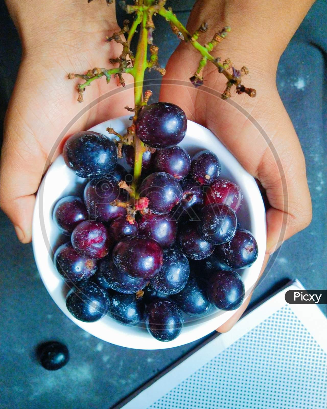 A bowl of fresh black  grapes.