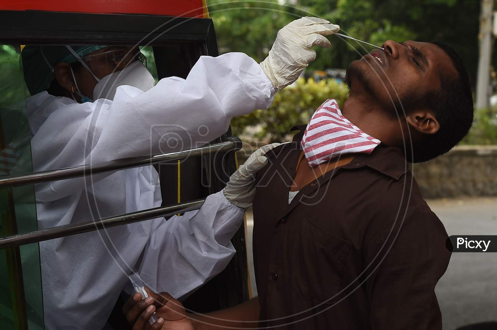 A Health Worker Wearing Personal Protective Equipments (Ppe) Suit, Sits In A Share Auto-Rickshaw As She Collects A Swab Sample From A Man To Test For The Covid-19 Coronavirus, Outside A Commercial Centre In Chennai On September .15.2020