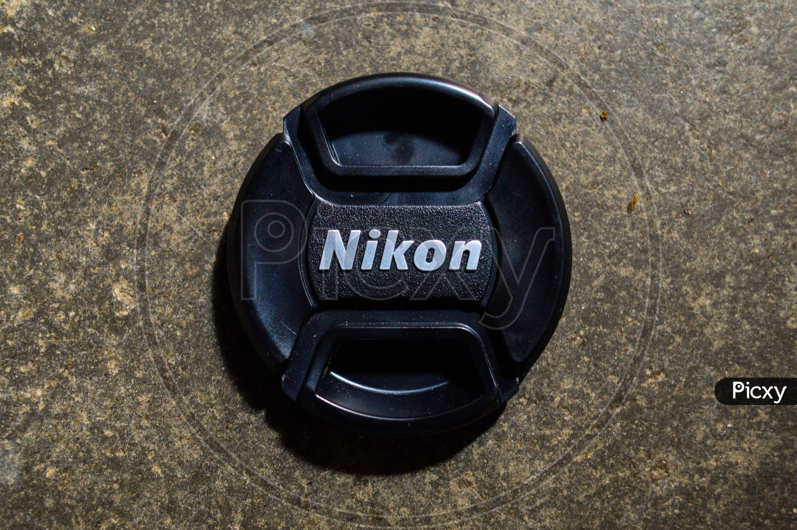 A Lens Cap Of Nikon Camera Lens Isolated On Texture Cemented Floor.