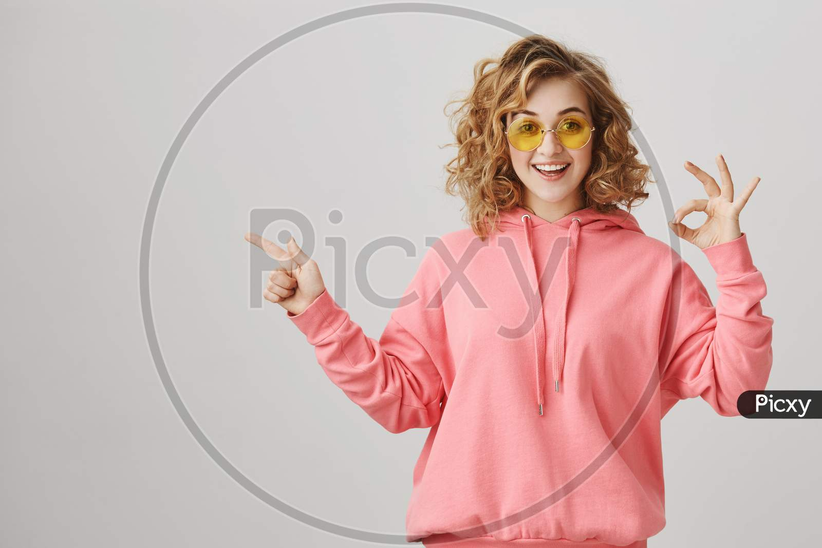 I Am Okay With That. Studio Shot Of Good-Looking Curly-Haired Girl With Bright Smile Showing Fine Gesture And Pointing Left With Friendly And Happy Expression, Standing Over Gray Background.