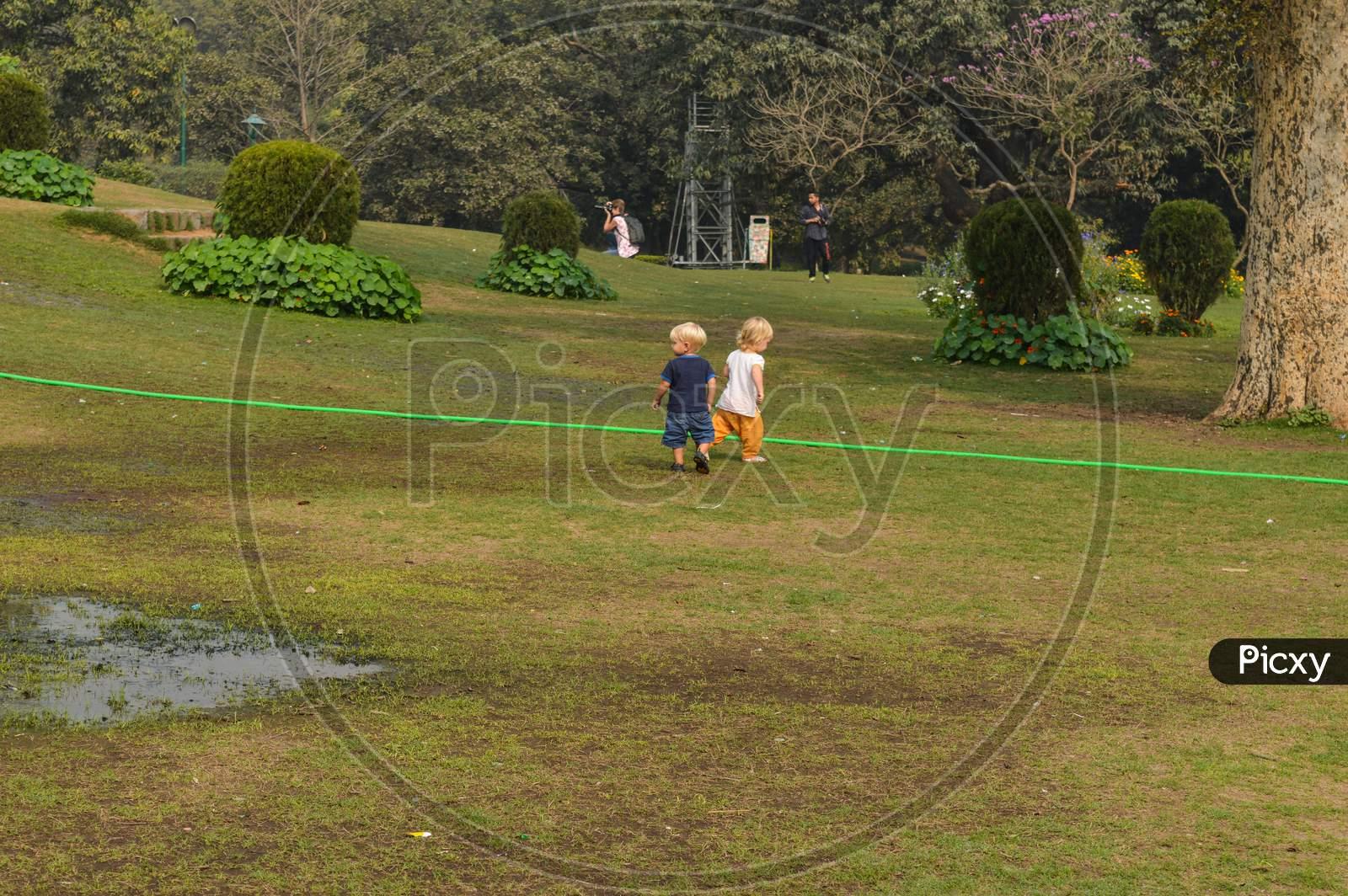 A Siblings Playing And Running At Park, Lawn At Winter Foggy Morning.