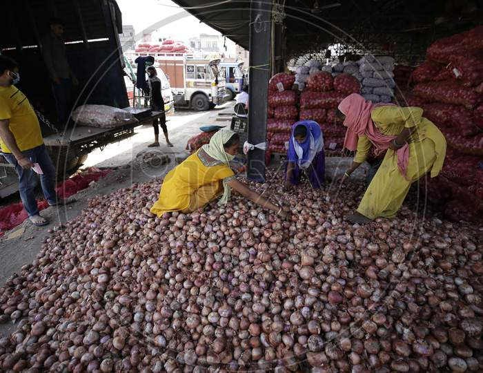 Workers sort onion at Narwal vegetable wholesale market on the outskirts of Jammu on September,17 2020.