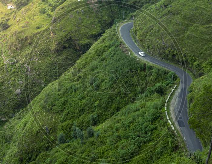 A Road In The Green Mountains With A Car.