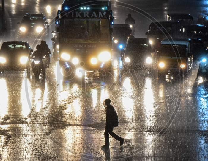 a man walks on the road at a traffic signal as it rains heavily in Hyderabad , September 16, 2020.
