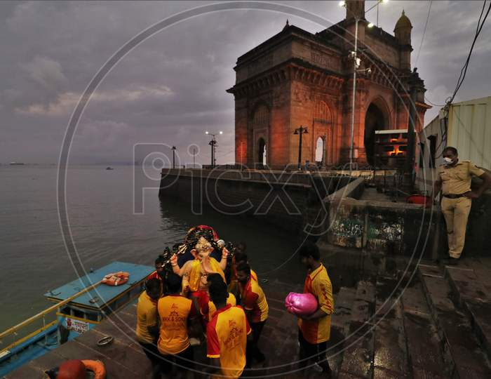 Volunteers carry an idol of Hindu God Ganesha, to immerse in the Arabian Sea, marking the end of the 10-day long Ganesh Chaturthi festival at the Gateway of India, in Mumbai, India on September 1, 2020