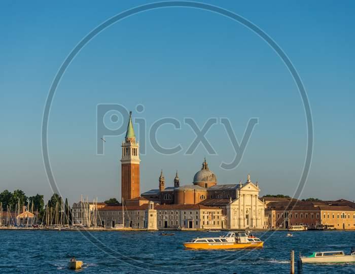 Venice, Italy - 30 June 2018: Gondolas Moored By Saint Mark Square With San Giorgio Di Maggiore Church In The Background In Venice, Italy