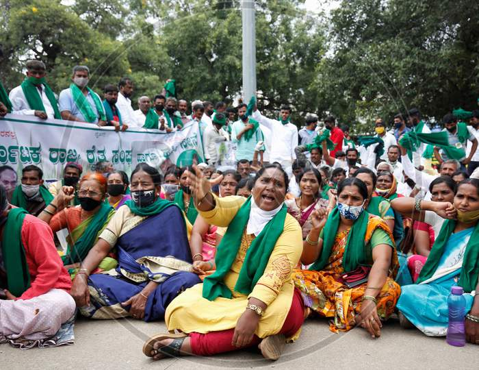 People chant slogans against the government and wave flags during a protest against the passage of two controversial farm bills by the country's parliament in Bangalore, India.
