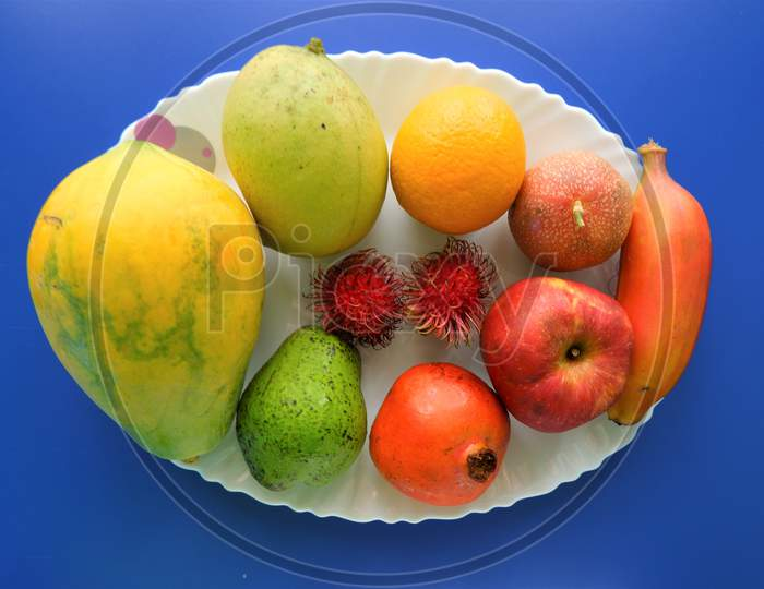 Healthy natural fruits on white plate ,top view,blue background