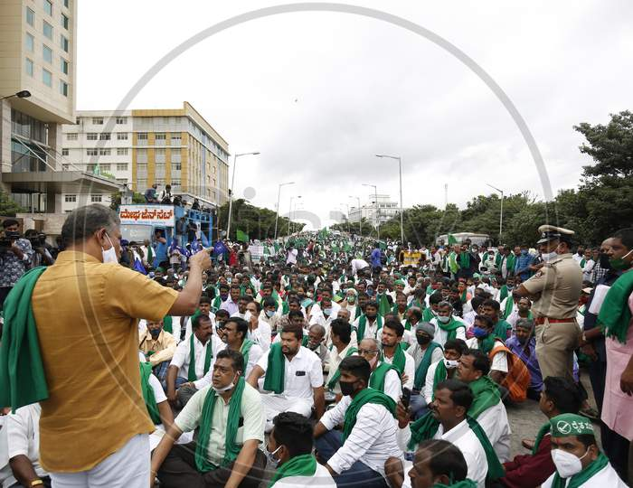 Farmers block a road as they listen to a party leader during a protest against the passage of two controversial farm bills by the country's parliament in Bangalore, India.