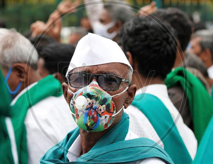 A farmer wears a Mickey Mouse mask to protect from the novel coronavirus during a protest against the passage of two controversial farm bills by the country's parliament in Bangalore, India.