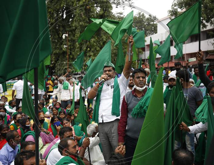 Farmers chant slogans against the government and wave flags during a protest against the passage of two controversial farm bills by the country's parliament in Bangalore, India.