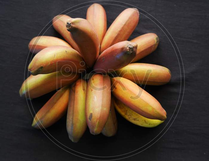 Bunch of red banana fruits ripened  isolated on black  background