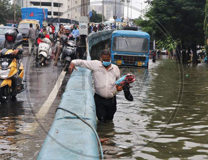 A man wades through a waterlogged road after heavy rainfall in Mumbai, India, September 23, 2020.