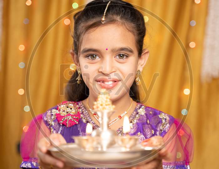 Pov Shot Of Cute Little Girl In Traditional Dress Doing Aarti Or Offering Light To God During Hindu Religious Festival Ceremony.