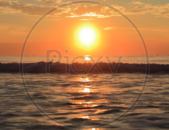 At Sunrise In The Morning, The Huge Bright Rays Of The Bright Sun Welcoming The Rising Waves Of The Huge Ocean