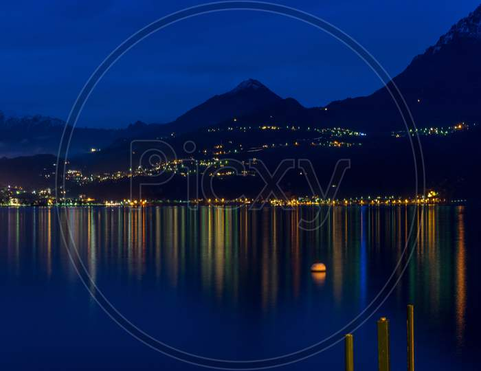 Italy, Varenna, Lake Como, A Large Body Of Water With A Mountain In The Dark