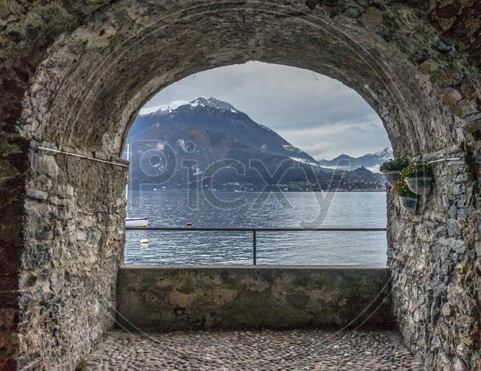 Italy, Varenna, Lake Como, Scenic View Of Sea Against Mountain Seen Through Arch