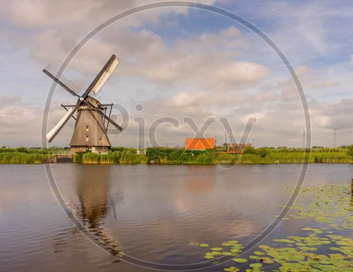 Netherlands, Rotterdam, Kinderdijk, Heritage Windmill Above Lush Green Grass Along A Canal With Reflection