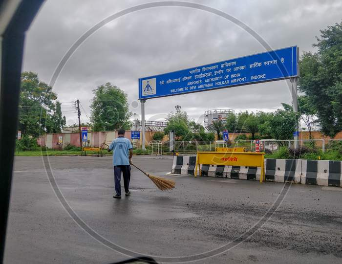 Indore, India - August 22Nd 2020: Worker Cleaning Road Outside Indore Airport.