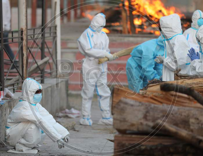 Relatives and health workers wearing protective suits cremate the  bodies of COVID-19 victims, at Jammu District,on 30 September,2020.