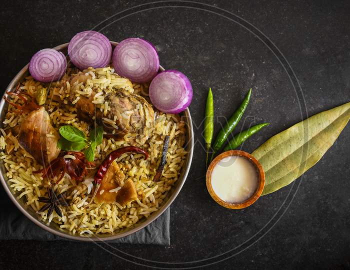 Delicious chicken biryani top view.Biryani rice dish Beautiful Indian rice dish.Delicious spicy chicken biryani in bowl over moody background, it's a popular Indian and Pakistani food.