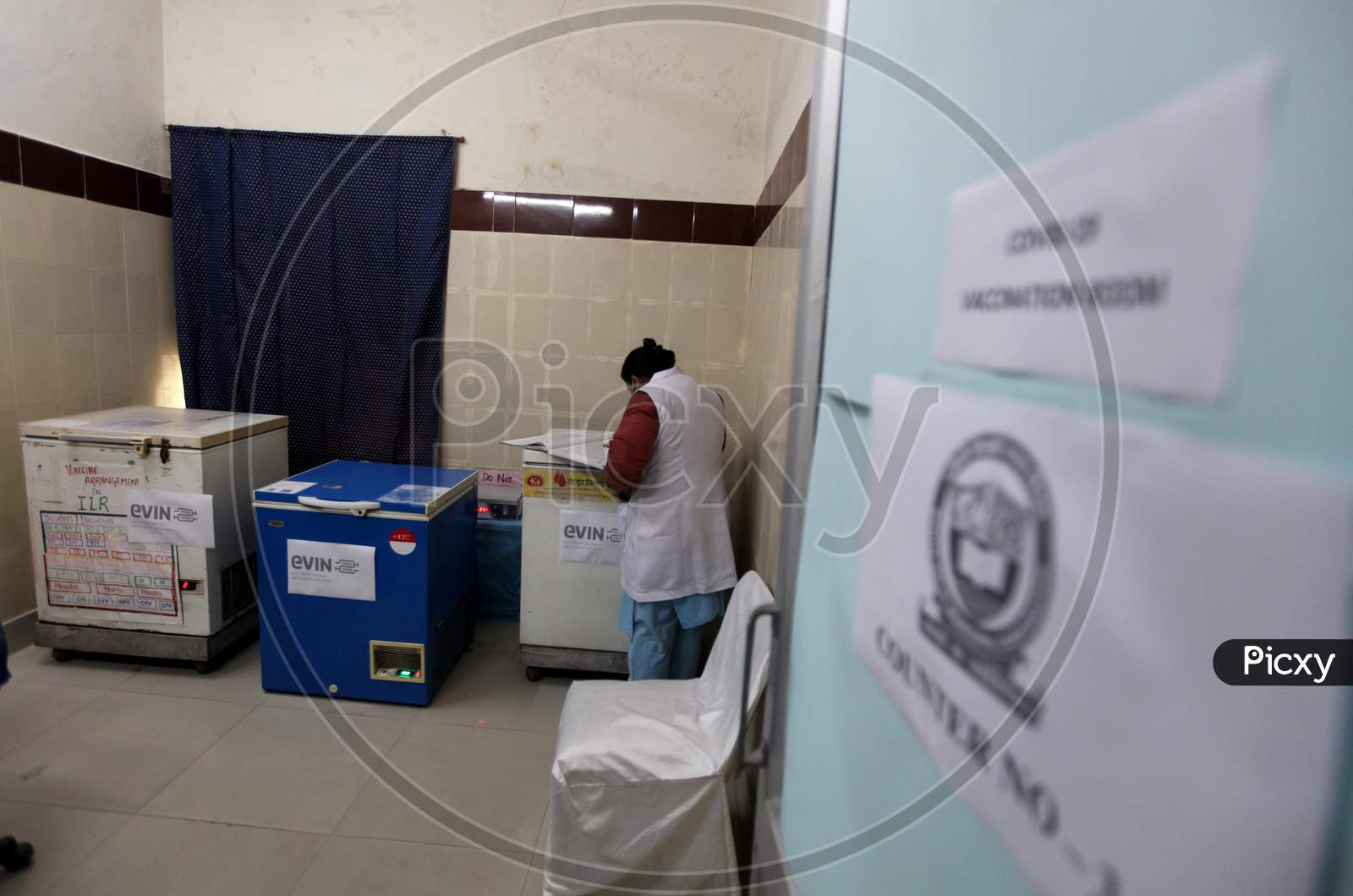 A healthcare worker make preparations inside a room at a vaccination center set up at a MCD maternity home ahead of a nationwide trial of a Covid-19 vaccine delivery system in New Delhi, India, on, Jan 1, 2021. India will test its Covid-19 vaccine delivery system with a nationwide trial on Jan 2.