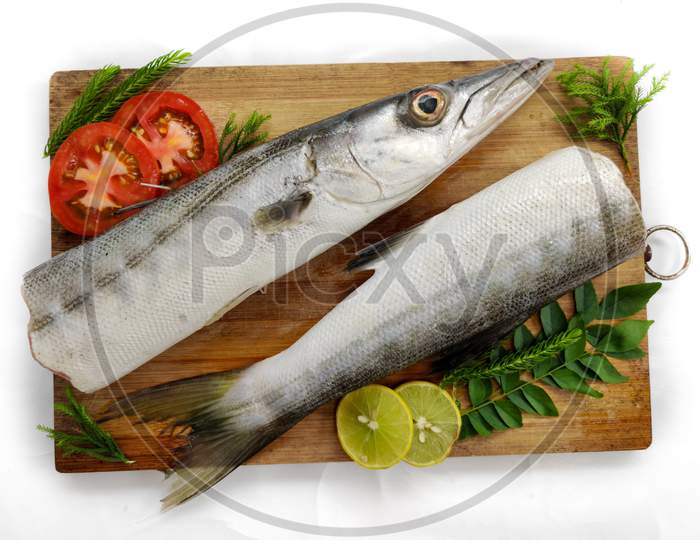 Fresh Raw Barracuda Fish (Cheelavu) Head And Body Decorated With Herbs And Vegetables On A White Background.Selective Focus.