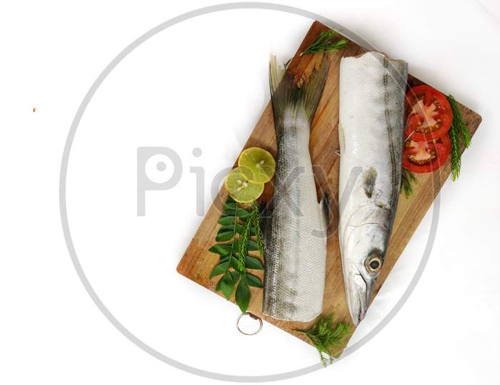 Fresh Raw Barracuda Fish (Cheelavu) Head And Body Decorated With Herbs And Vegetables On A White Background.Selective Focus.Space For Text.