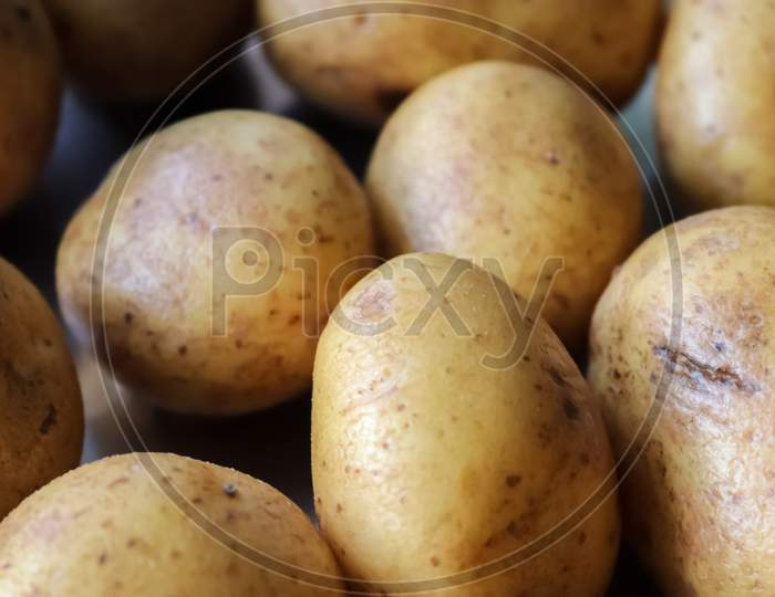 Top View At Uncooked Potatoes On A Metallic Surface. Kitchen Concept