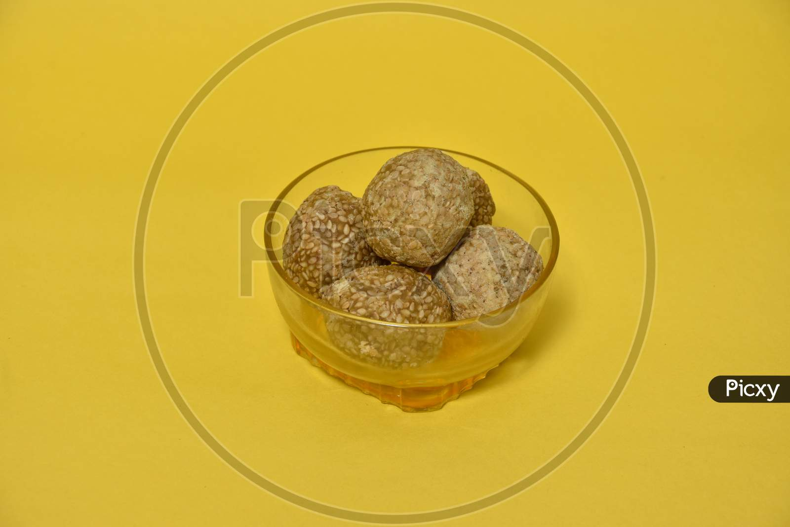 Indian sweet Sesame seeds ball or called in Hindi til ke laddu in glass bowl on yellow background.