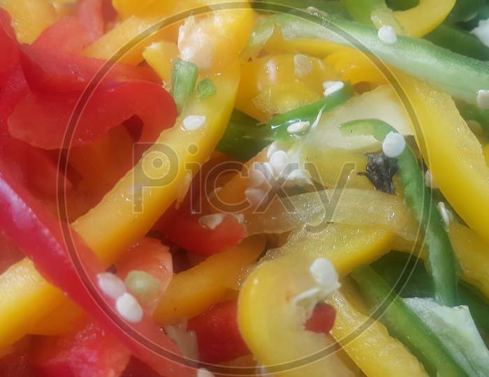 Slices Of Colorful Green, Yellow, Red, Purple Hot Shiny Shimla Chilli Or Peppers