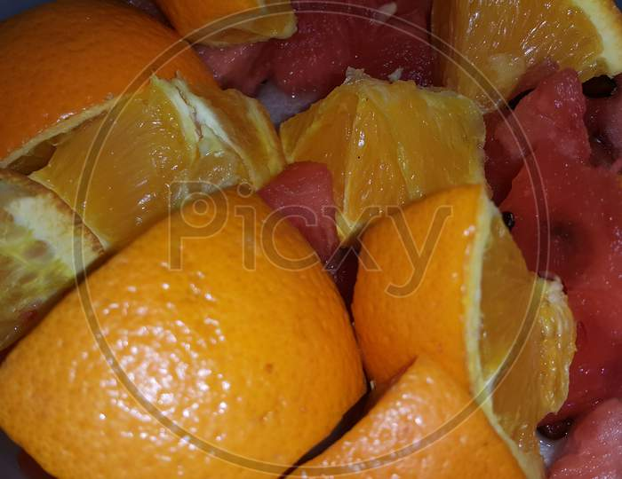 Closeup View Of Mixed Fruits Slices Of Citrus Oranges And Sweet Red Watermelon
