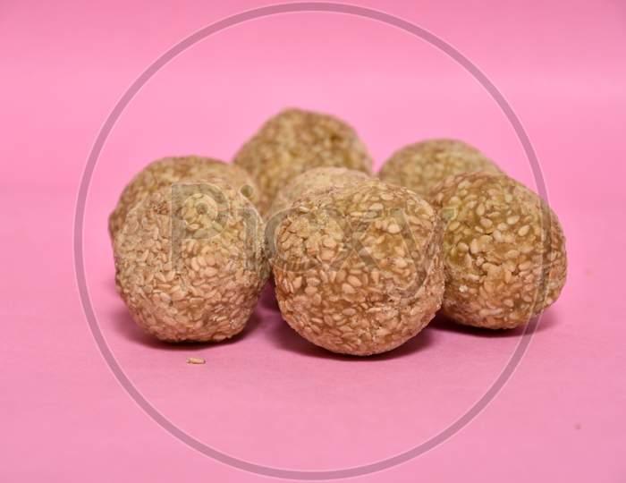 Indian sweet dish,Sesame seeds ball or called in hindi, til ke laddu on pink background.