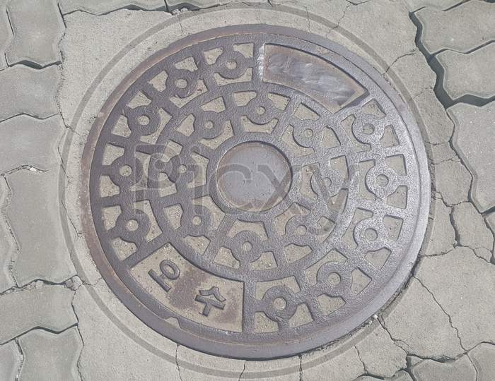 Top View Of A Manhole Cover On Drainage Or Sewerage Under Paved Road.