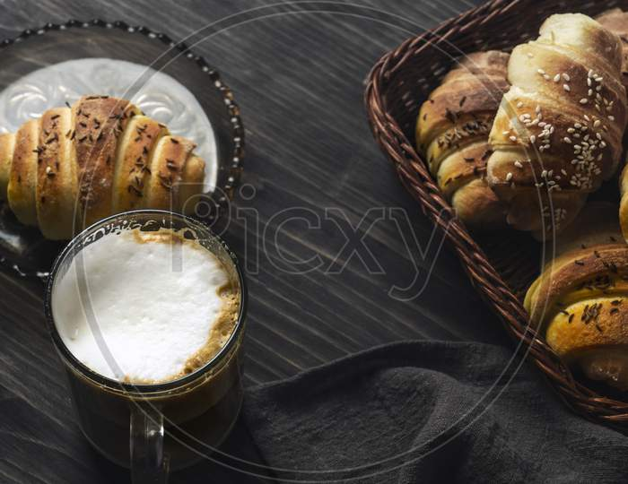 Homemade Buns And Coffee On Wooden Table