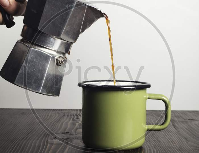 Hand Close Up Pouring Espresso Coffee In A Cup