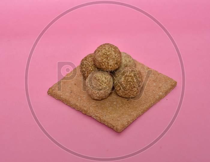 Indian sweet dish,Sesame seeds ball or called in hindi, til ke laddu on pink background