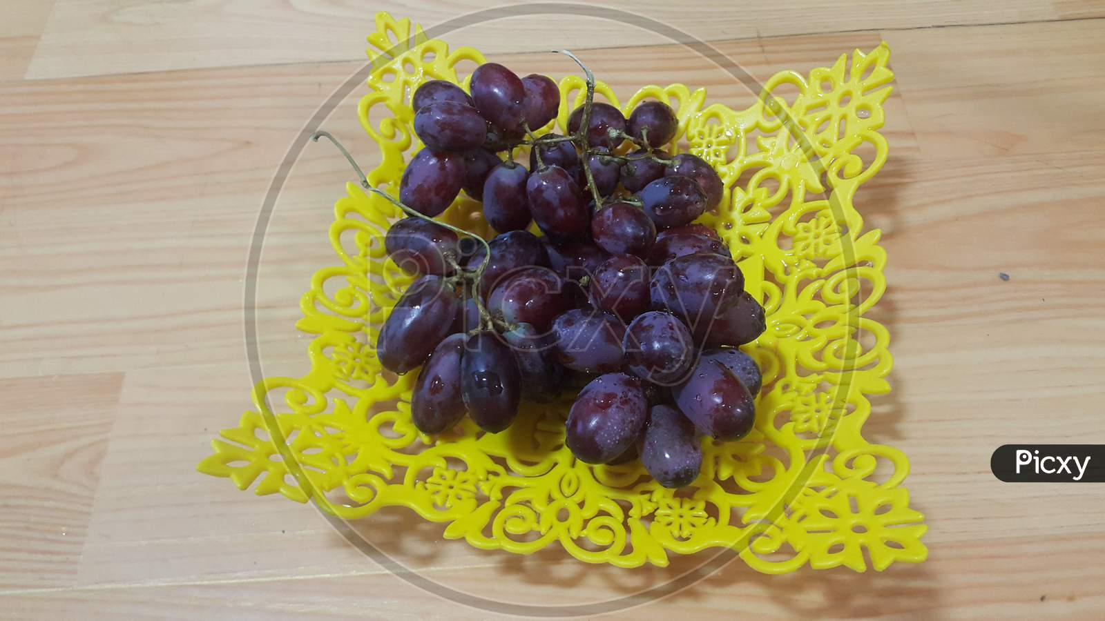 Close Up View Of Bunches Of Brown Grapes Served In Yellow Plastic Fruit Tray