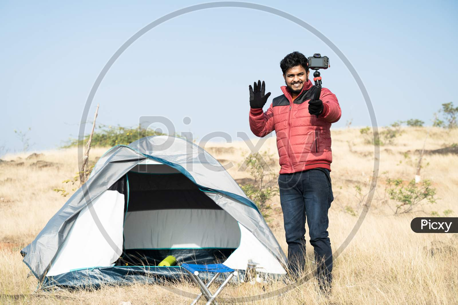 Wide Angle Shot Of Young Traveller Busy Talking With Camera On Top Of Mountain In Front Of Camping Tent - Concept Of Travel Vlogger, Blogger Or Influencer Recording Video During Hiking.