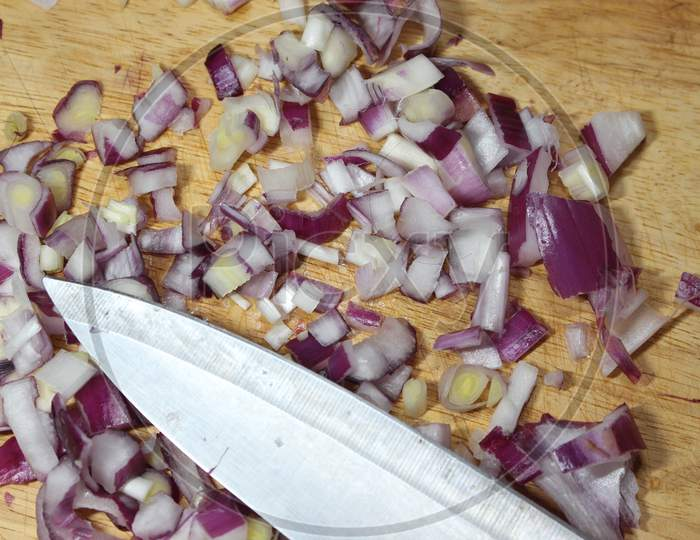 Chopped White Onion With Sharp Knife On Wooden Cutting Board